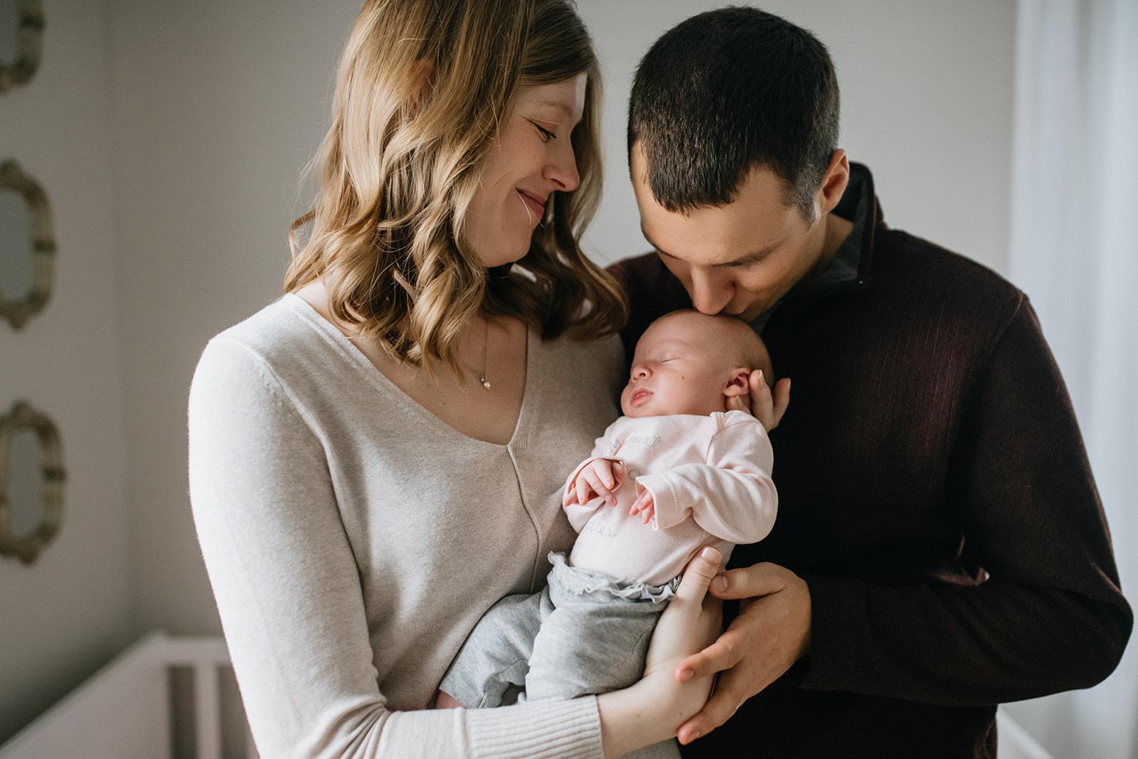 Proud parents hold & kiss newborn baby